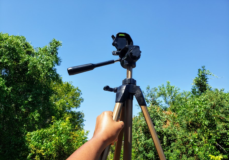 Camera tripod against the blue sky. At the park.