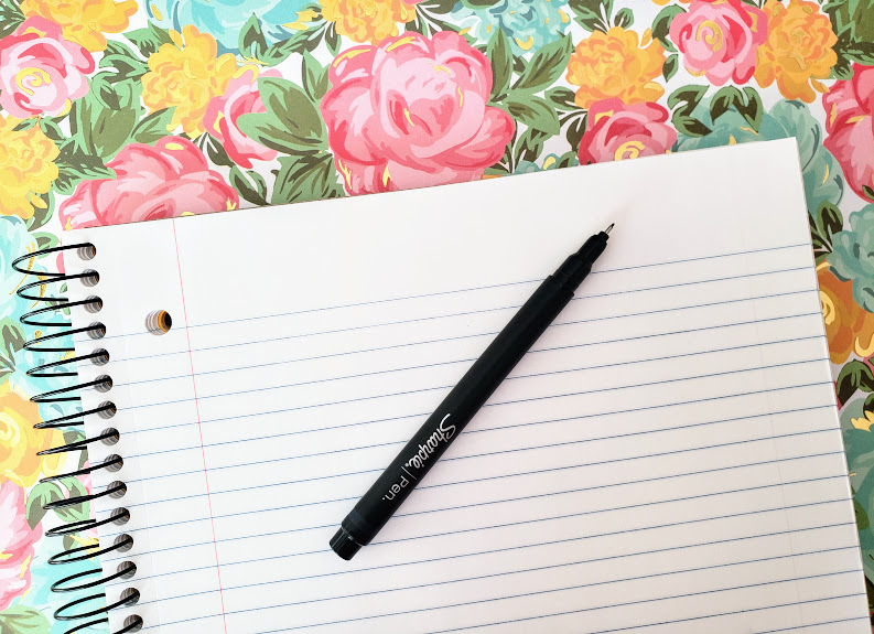 Writing tablet and pen on a floral background.