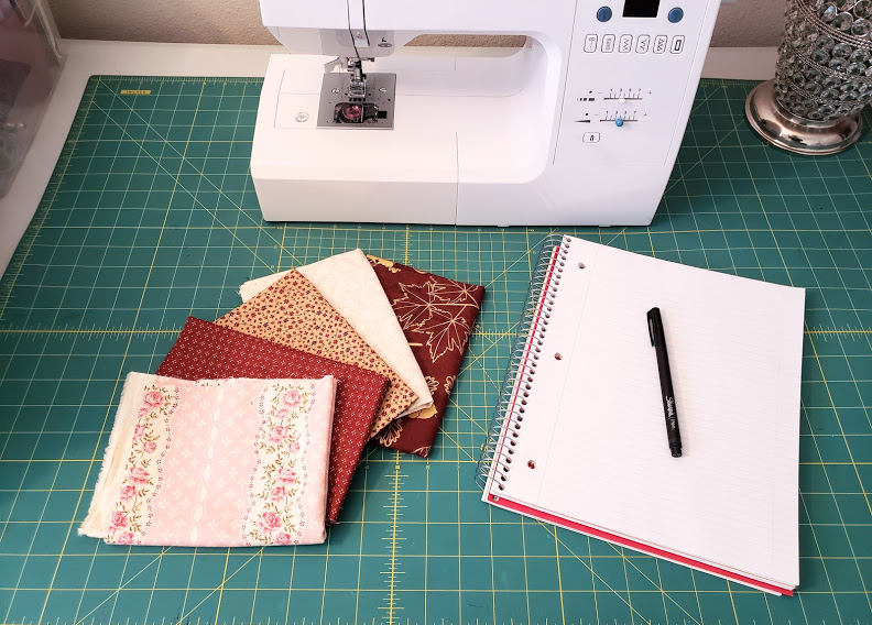 Fabric samples, notebook and pen, and sewing machine.